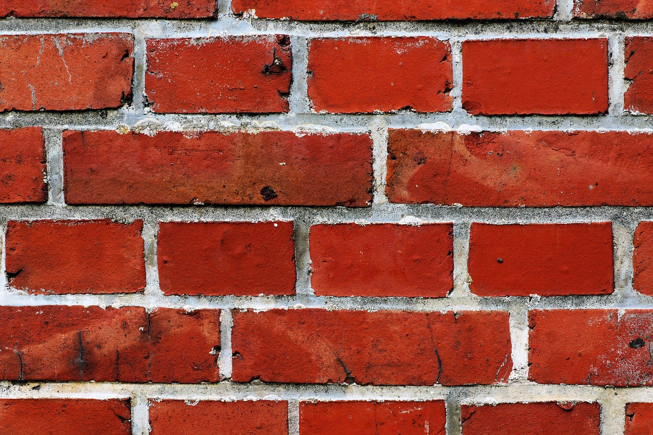 A brick wall showing signs of worn and damaged mortar